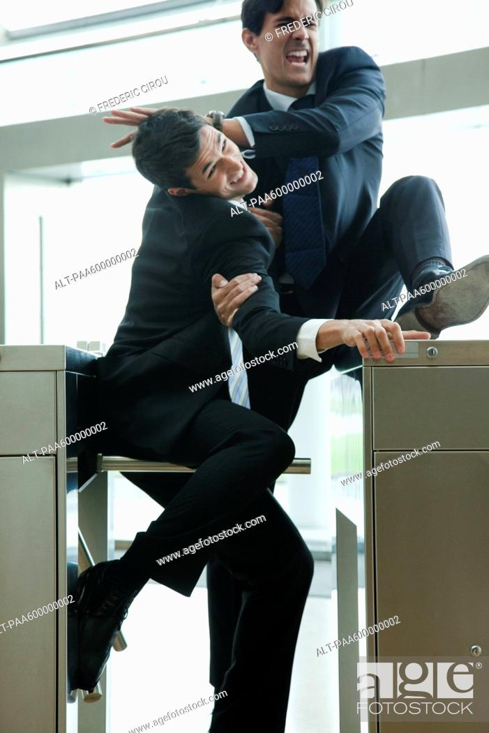 Stock Photo: Businessmen fighting to beat each other through turnstile.