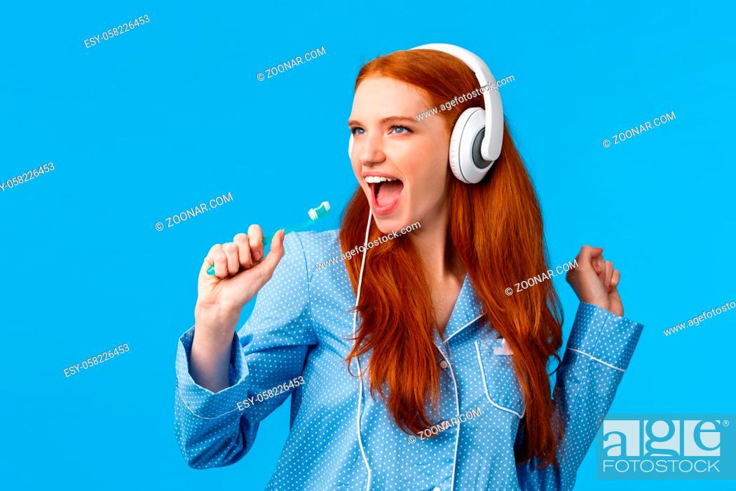 Stock Photo: Sassy good-looking redhead female in pyjama having fun, listening music in big white headphones, singing into toothbrush as brushing teeth, getting ready go out.