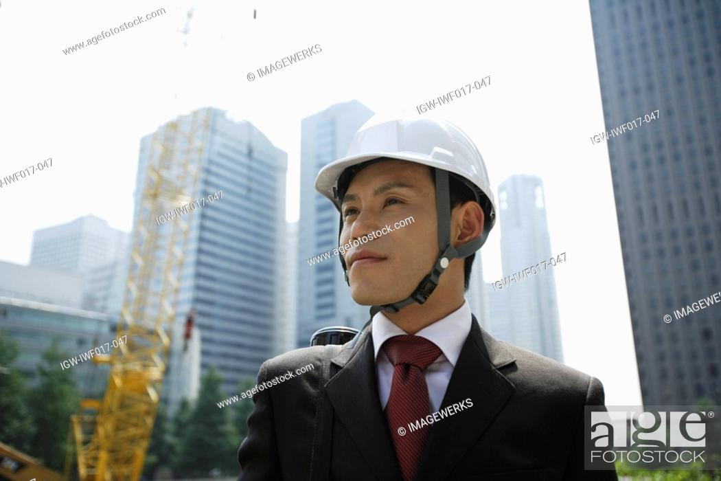 Stock Photo: Businessman with a hard hat, portrait.
