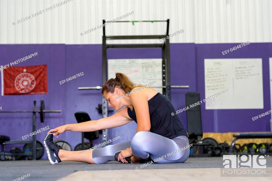 Stock Photo: Fit woman stretching before a workout at a crossfit gym in Oregon.