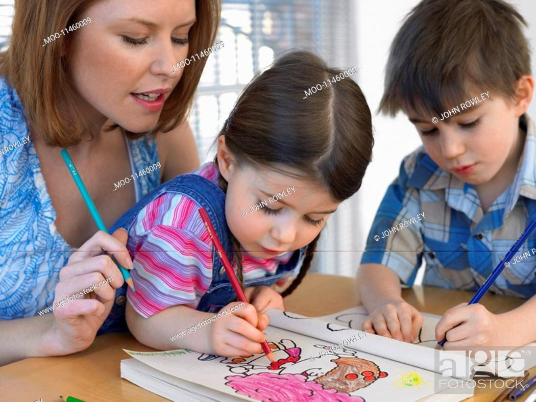 Stock Photo: Mother and children 3-6 colouring in book at home.