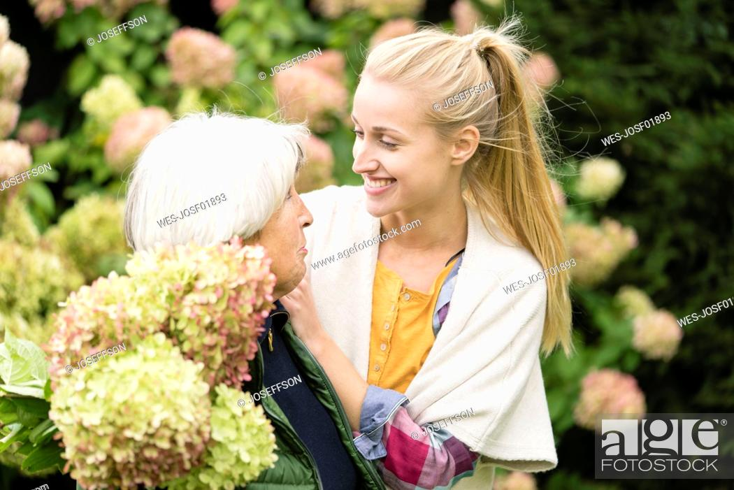 Stock Photo: Happy young woman with her grandmother at bush in garden.