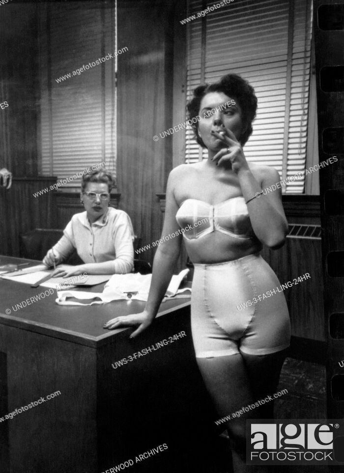 Stock Photo: Chicago, Illinois: 1949 A fashion model wearing a strapless bra and girdle, standing in an office smoking.