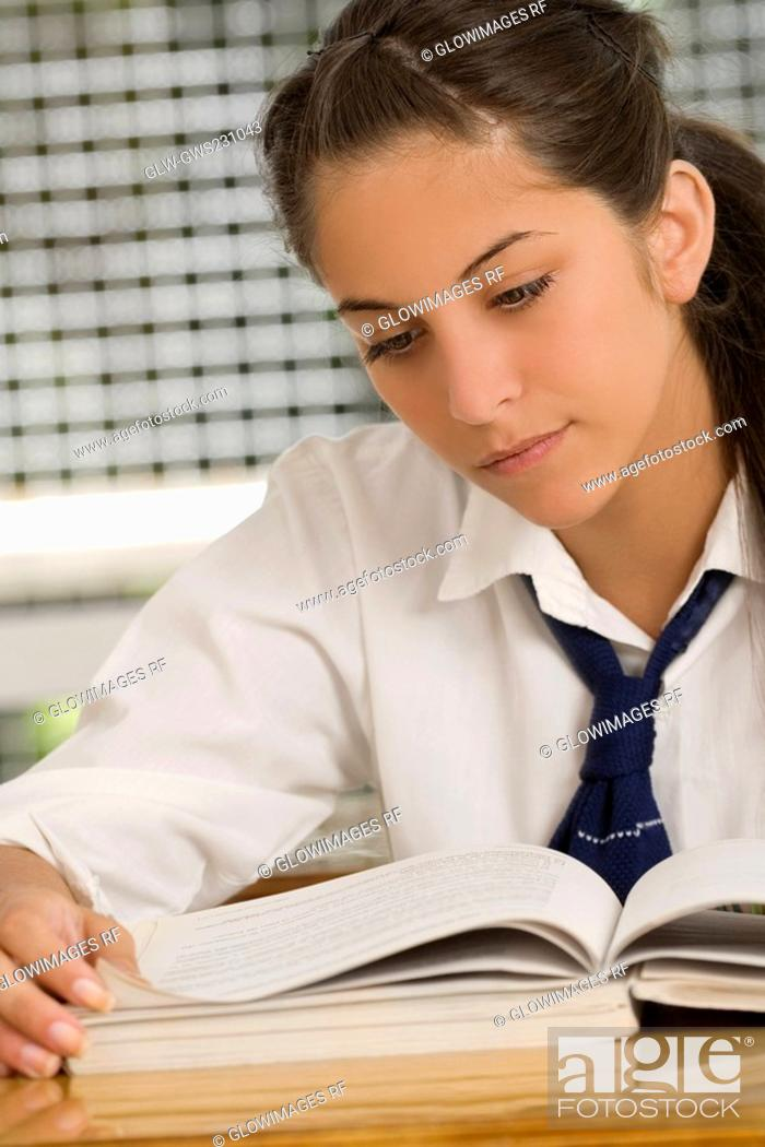 Stock Photo: Close-up of a teenage girl reading a textbook.
