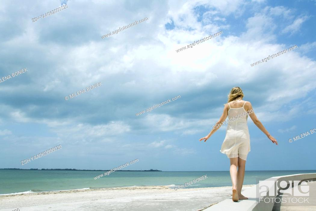 Stock Photo: Young woman in sundress walking along low wall at the beach, arms out, rear view.