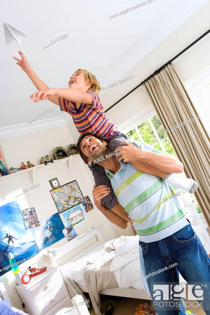 Stock Photo: Son 6-8 on father's shoulders, playing with paper dart tilt.