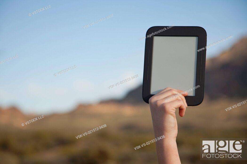 Stock Photo: USA, Arizona, Phoenix, Hand holding digital tablet in mountain area.