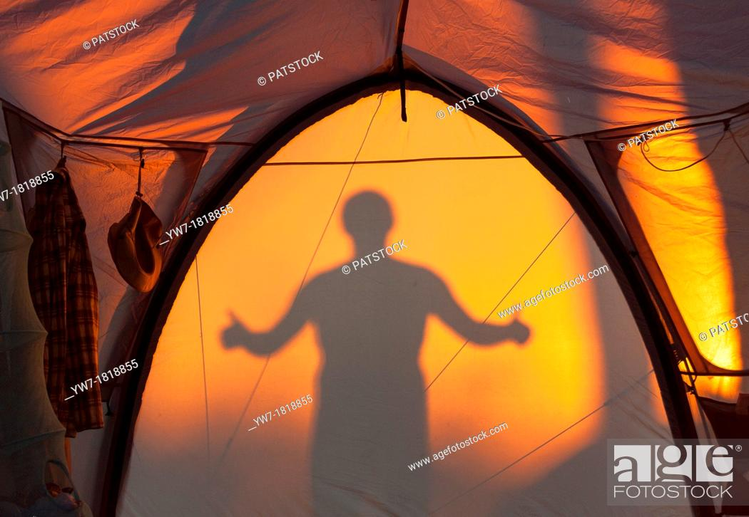 Imagen: Silhouette of man gesturing ok reflected on a tent.