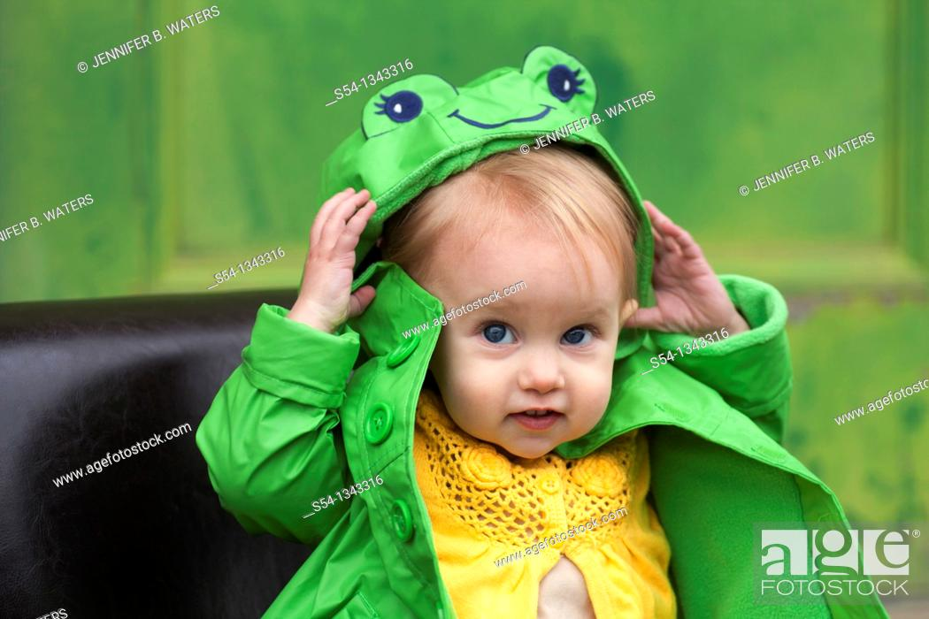 Stock Photo: A toddler outdoors in a bright green raincoat.