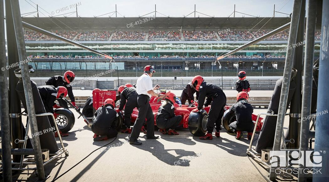 Stock Photo: Manager and pit crew replacing tires on formula one race car in pit lane.