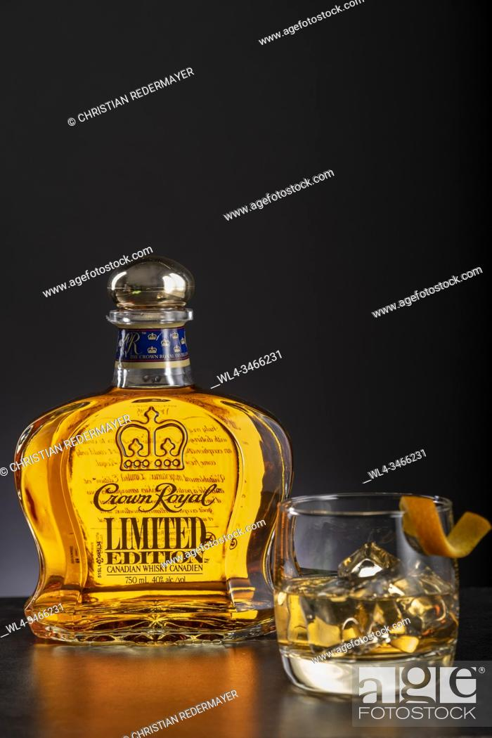 Stock Photo: Whiskey and one glass on wooden black background.
