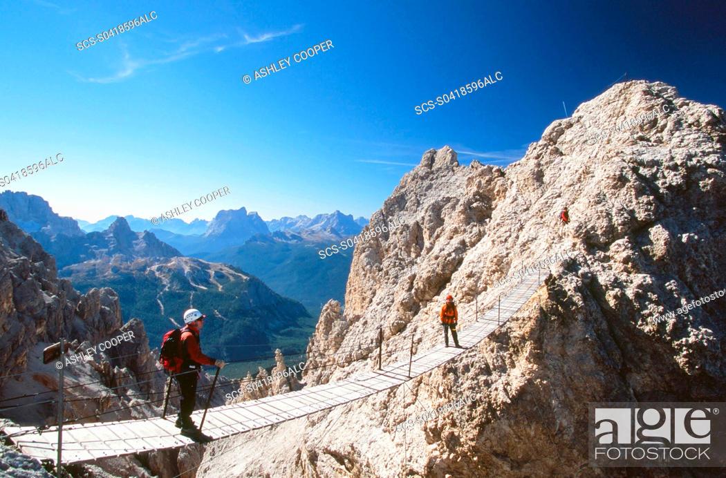 Stock Photo: A mountaineer on a via ferrata bridge in the Italian Dolomites.