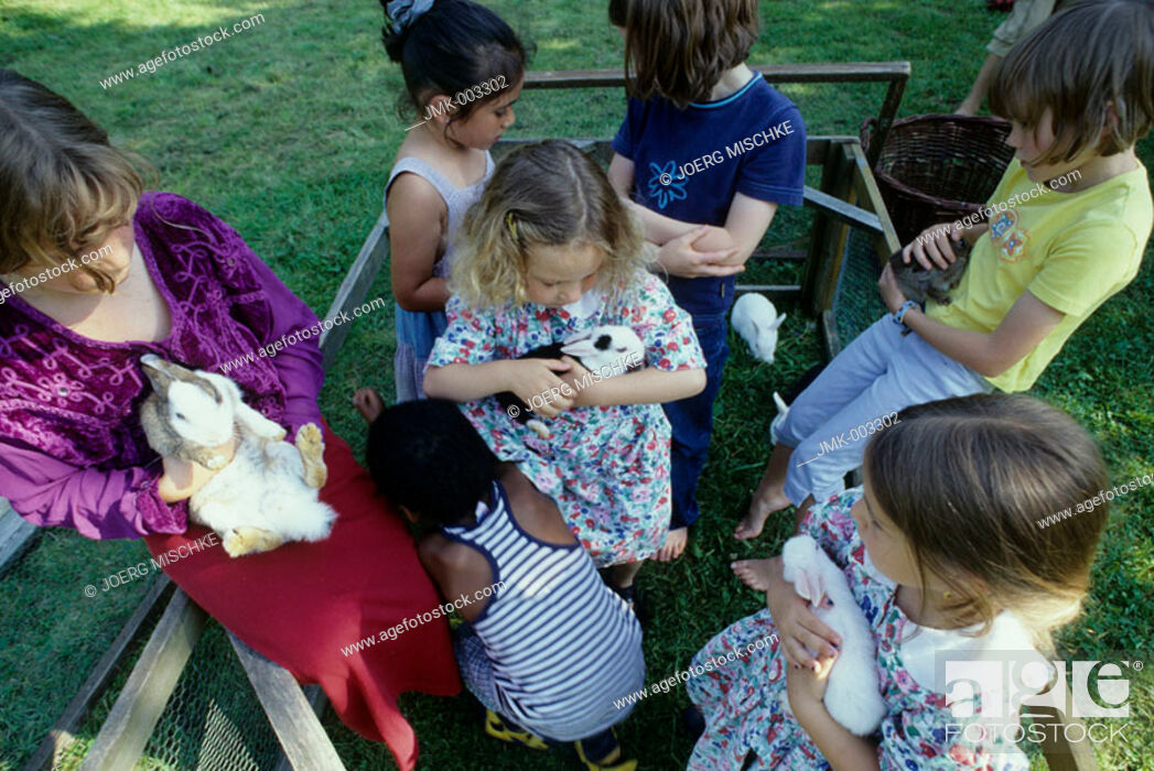 Stock Photo: Seven children, 1-5 5-10 years old, playing with rabbits, bunnies, in the garden in summer.