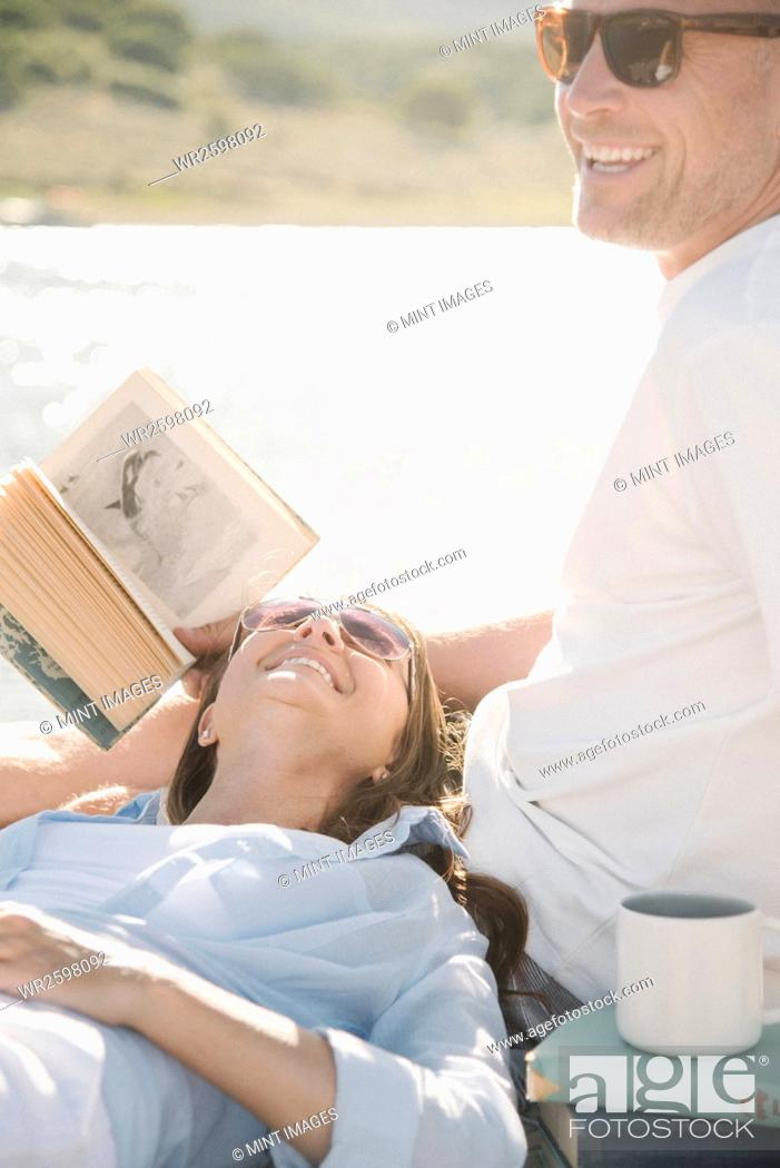 Imagen: Man and woman reclining on a jetty, reading a book.