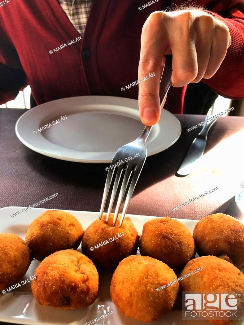Stock Photo: Man eating croquettes in a restaurant. Spain.