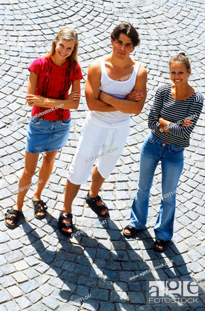 Stock Photo: High angle view of two young women and a young man standing with their arms folded.