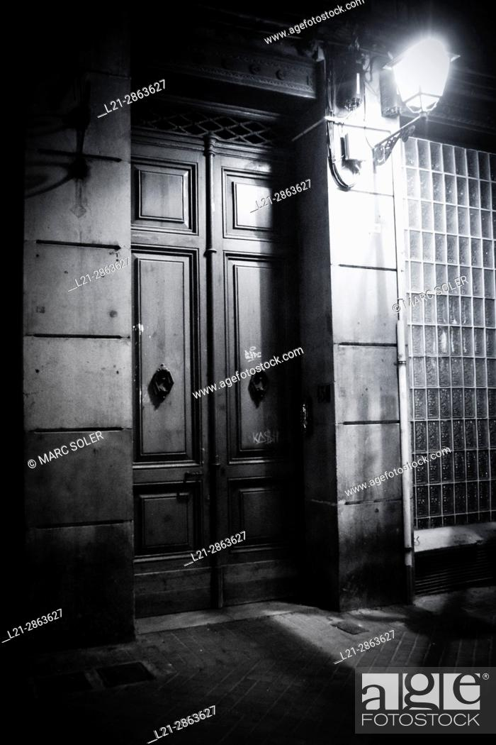 Stock Photo: Closed doors. Entrance of a house and streetlight lit at night. Barcelona, Catalonia, Spain.