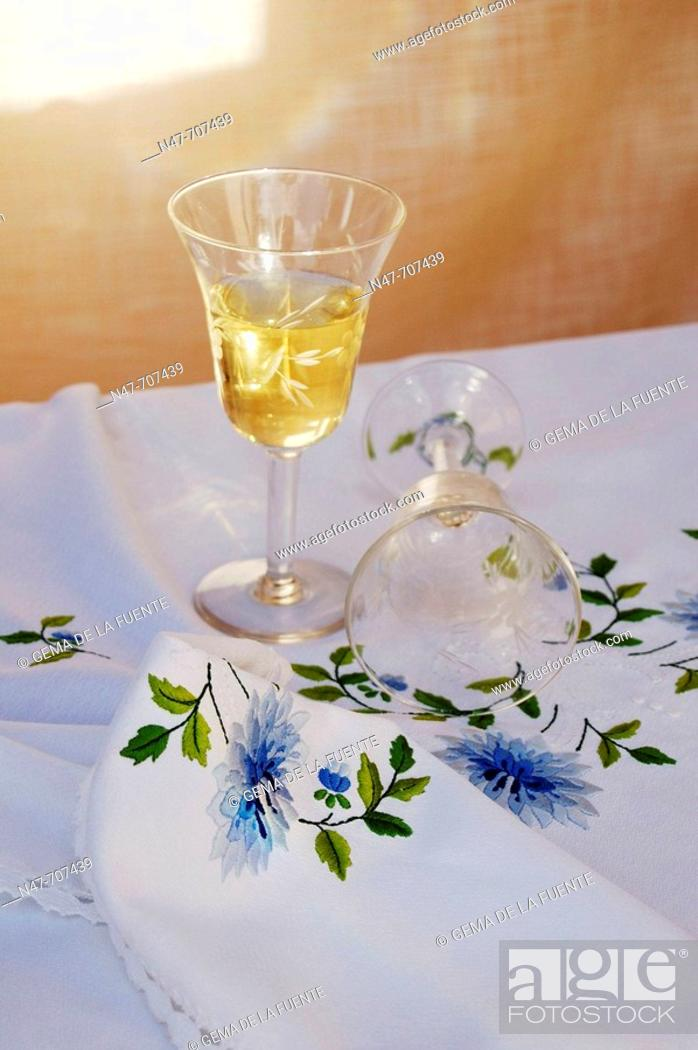 Stock Photo: Glasses on embroidered tablecloth.