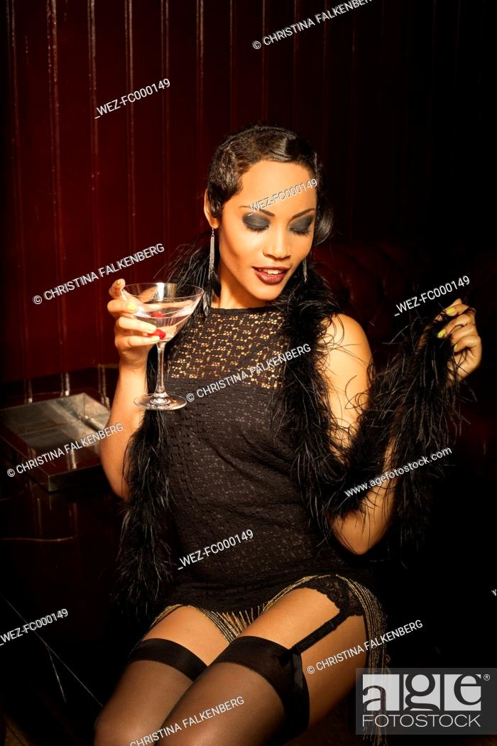 Stock Photo - Young female Afro-American styled in the way of roaring  Twenties sitting in a bar