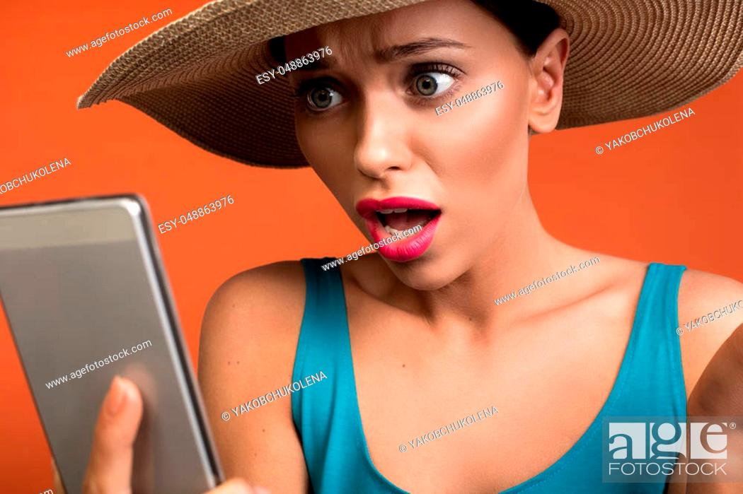 Stock Photo: Close up of female person with amazed expression looking at cellphone with daze. Isolated on background.