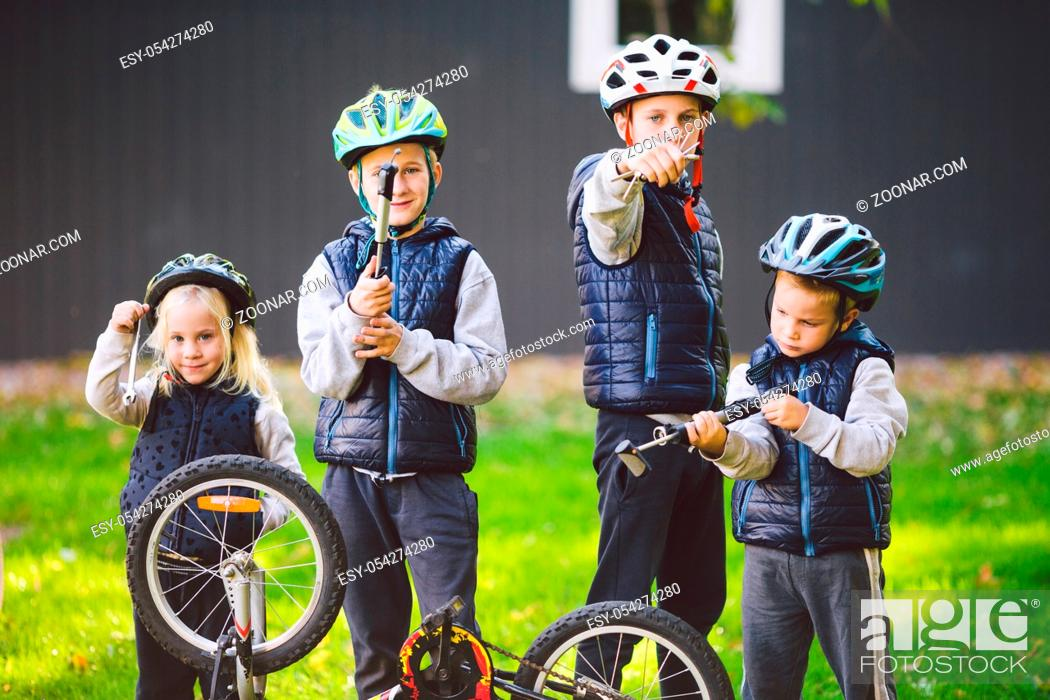 Stock Photo: Children mechanics, bicycle repair. Happy kids fixing bike together outdoors in sunny day. Bicycle repair concept. Teamwork family posing with tools for.