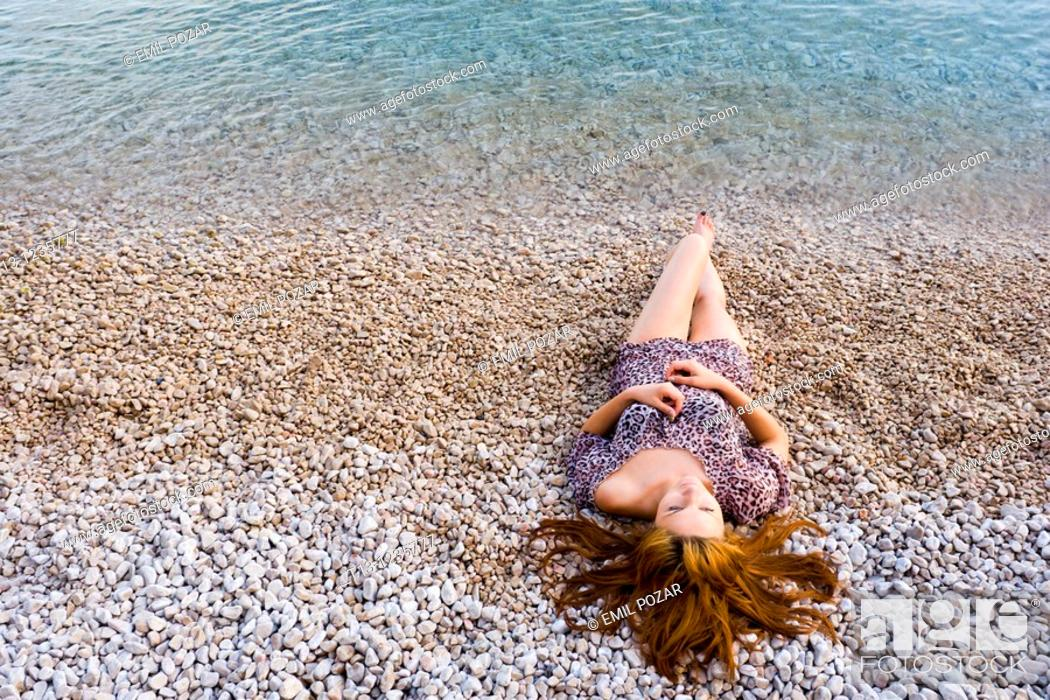 Stock Photo: Young woman is lying on the beach with her hair spread on sand.
