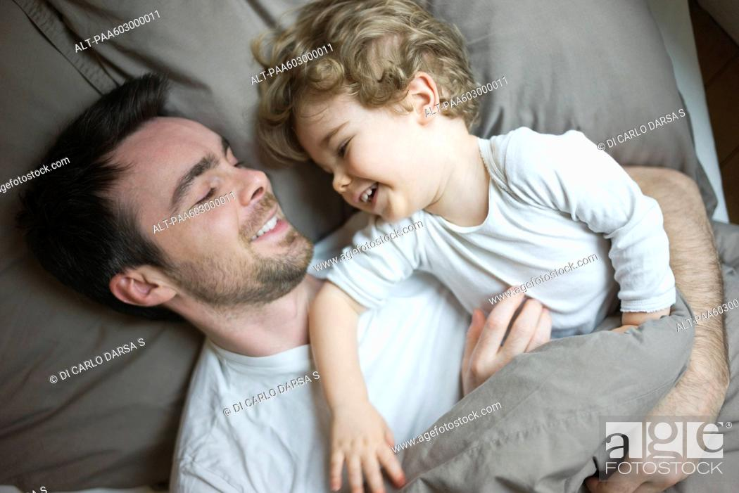Stock Photo: Father and young son relaxing together in bed, portrait.