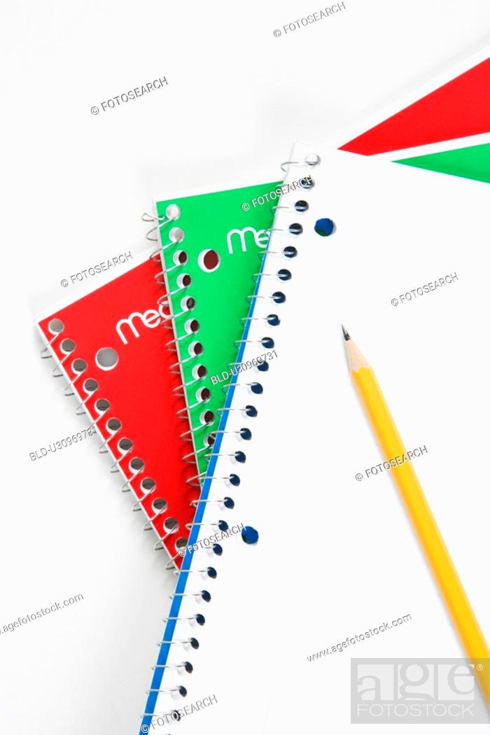 Stock Photo: Pencil on top of three spiral bound notebooks.