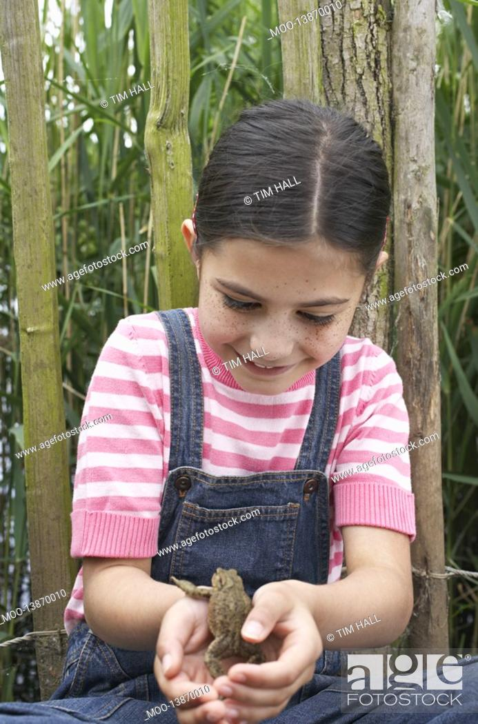 Stock Photo: Girl 5-6 holding toad by fence.