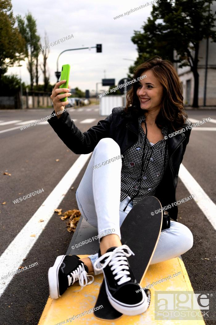 Stock Photo: Smiling young woman with skateboard sitting on bollard taking selfie with smartphone.