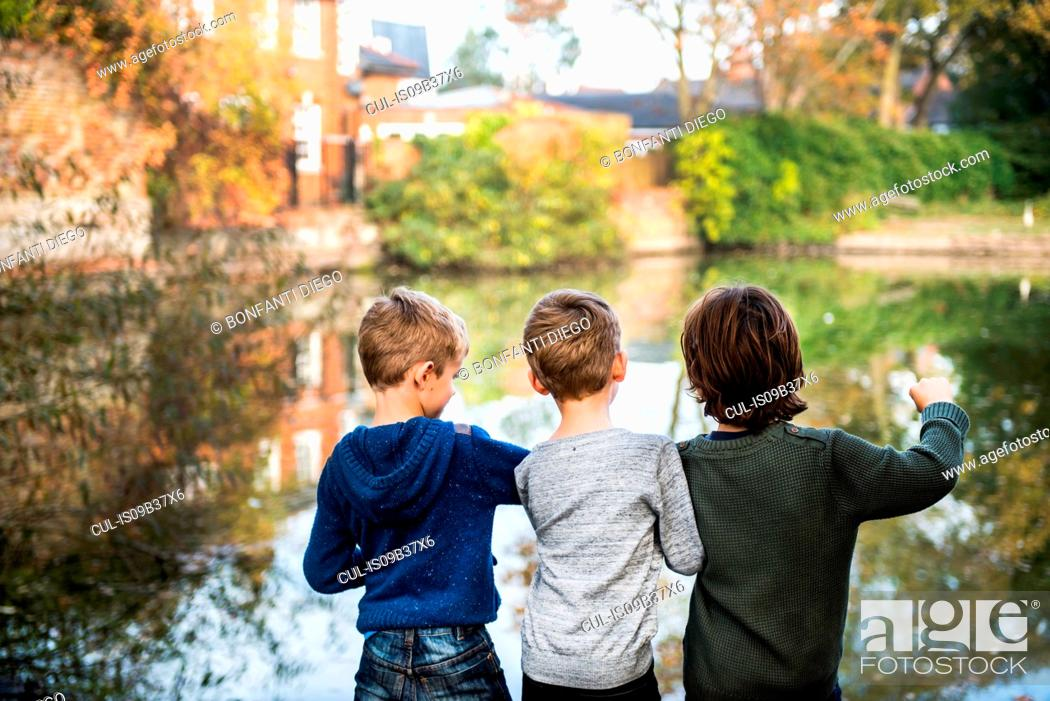 Photo de stock: Three young boys, standing beside lake, rear view.