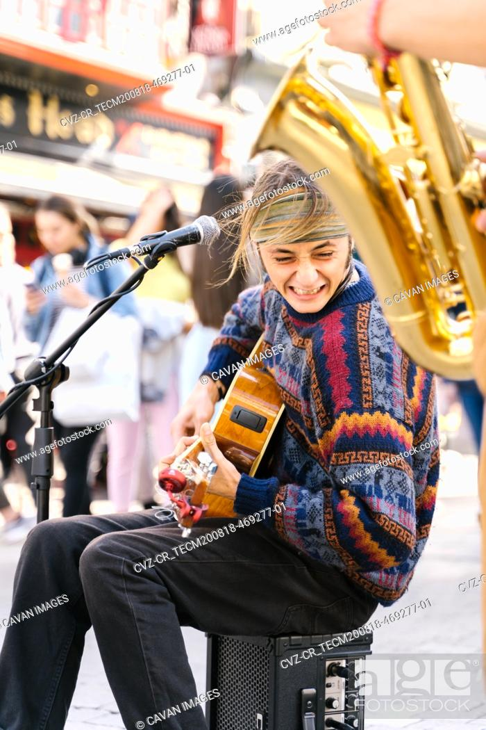 Imagen: Vertical photo of a young man singing while playing guitar next to a saxophonist in the street.