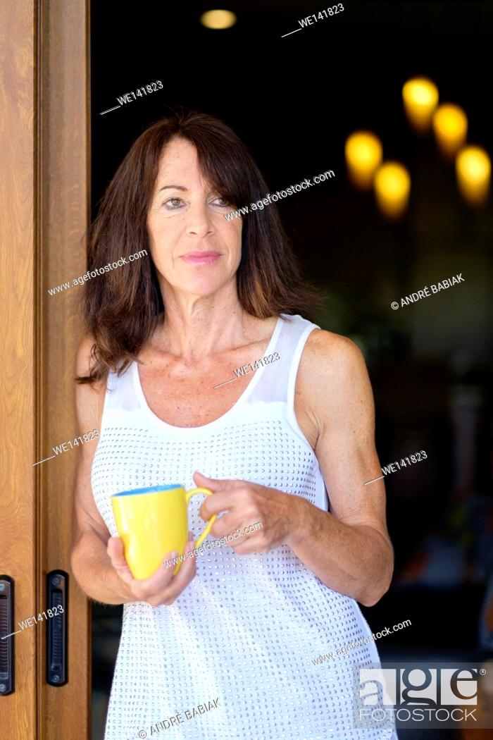 Stock Photo: Mature woman leaning against a door frame while holding a coffee mug.