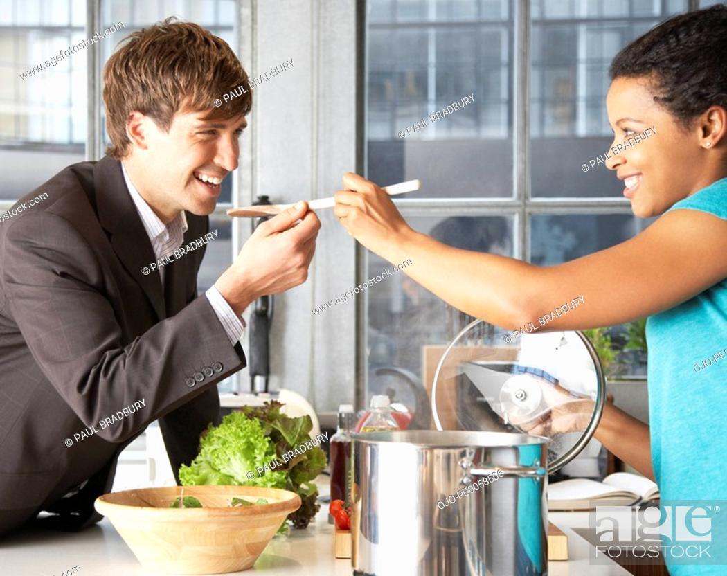 Stock Photo: Woman feeding man with a spoon.