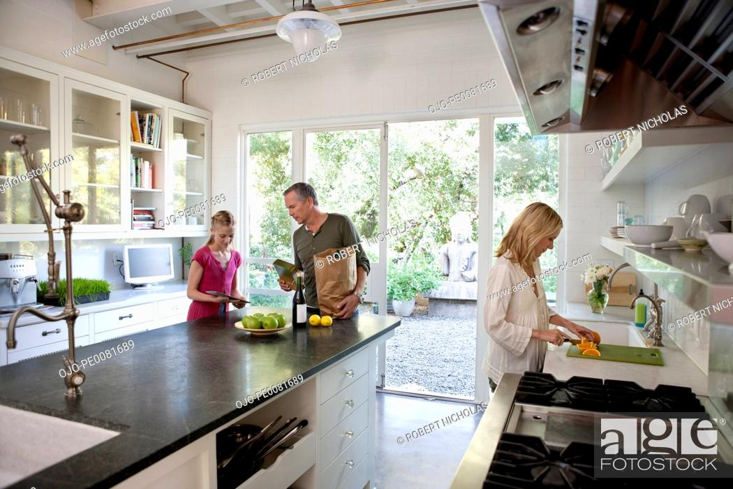 Stock Photo: Family unpacking groceries in kitchen.