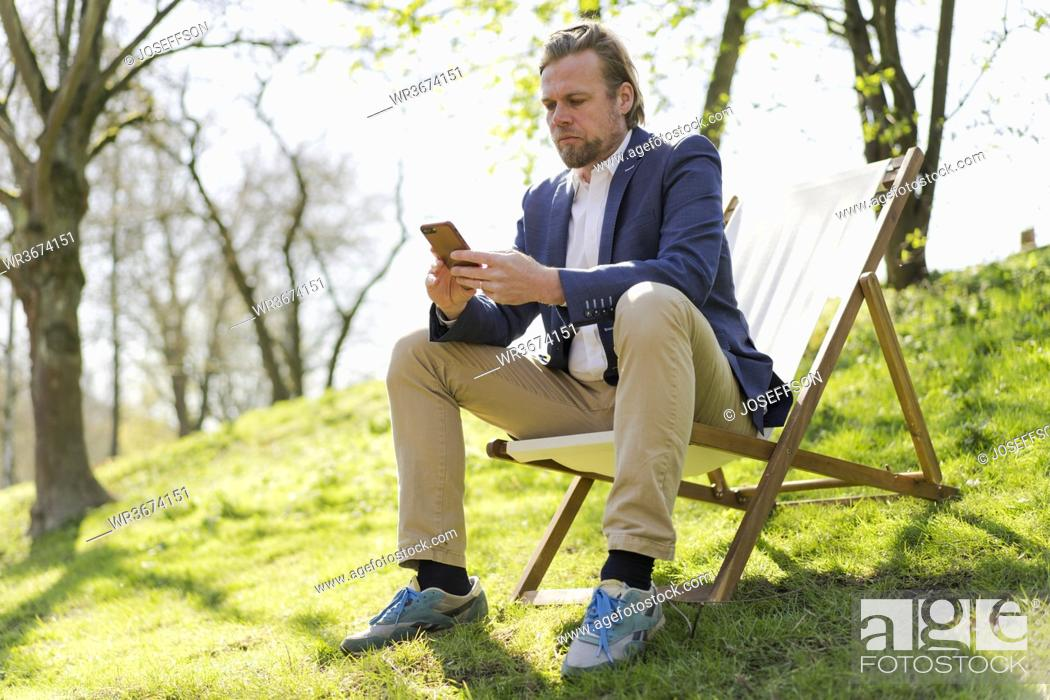 Stock Photo: Male entrepreneur using smart phone while sitting on chair at park.