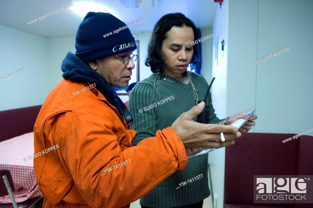 Stock Photo: Baltic Sea near Sweden. Two Indonesian sailors, known as: 'Able Seamen' are reviewing the loading-manifest for the loading and unloading of containers in the.