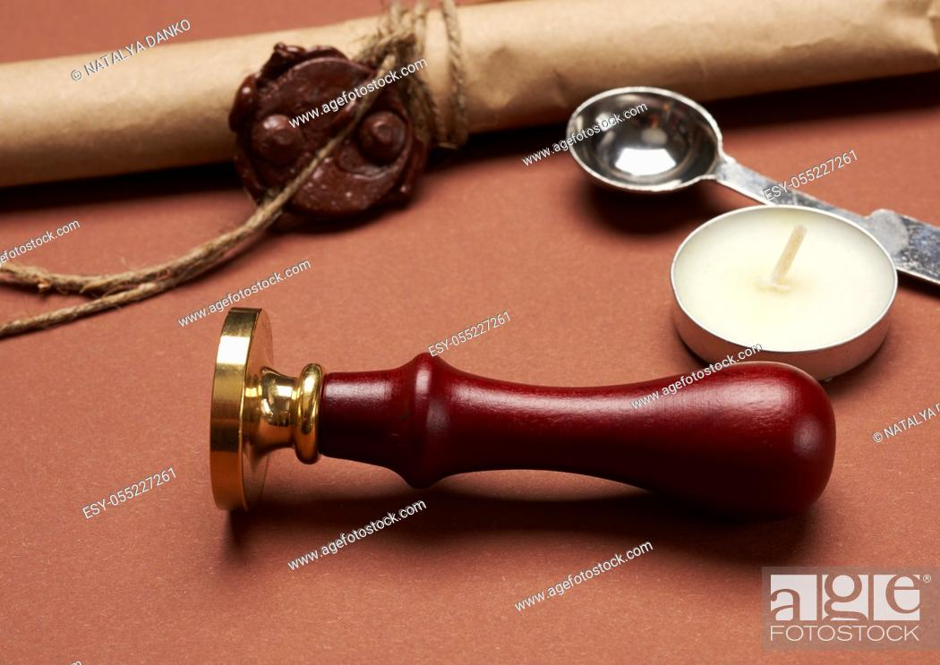 Stock Photo: metal stamp on wooden handle for sealing envelope, candle and brown paper roll, brown background.