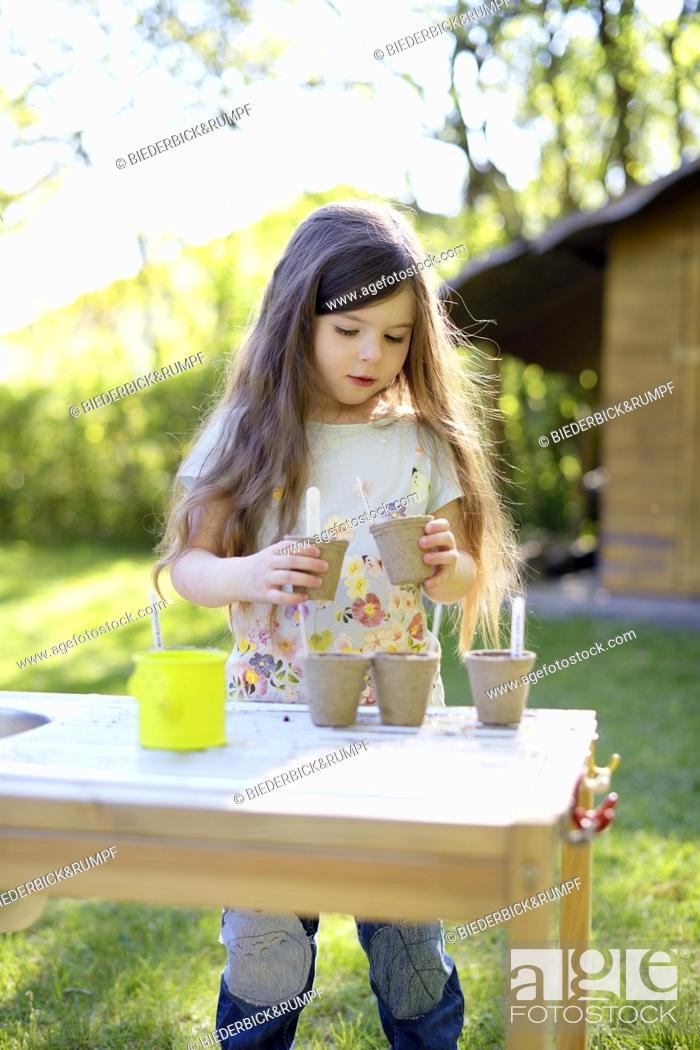Stock Photo: Cute girl planting seeds in small pots while standing at table in yard.