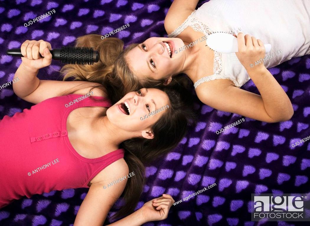 Stock Photo: Girls singing into hairbrushes.