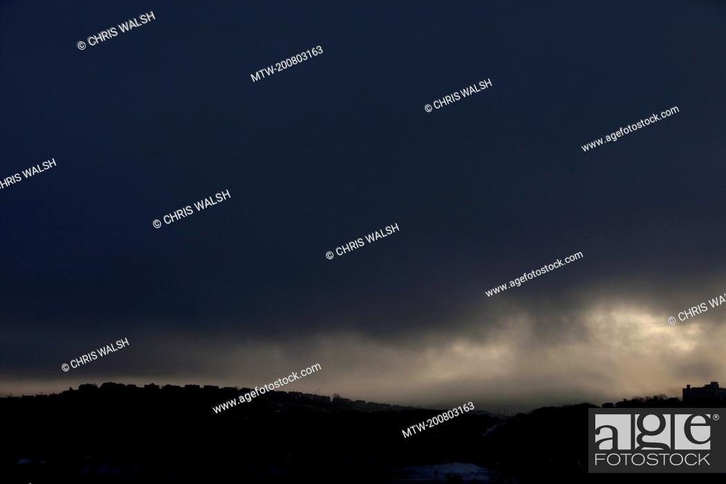 Imagen: Silhouette row houses dark sky stormy overcast.