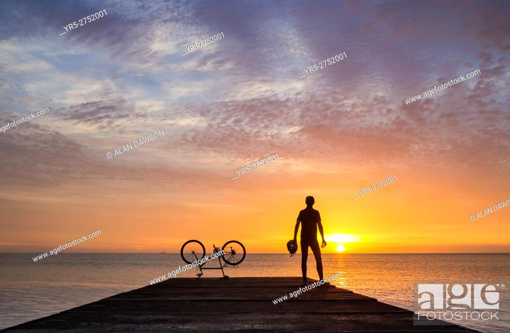Stock Photo: A mountain biker watches the sun rise over the North sea on a calm and tranquil morning at Seaton Carew, north east England, United Kingdom.