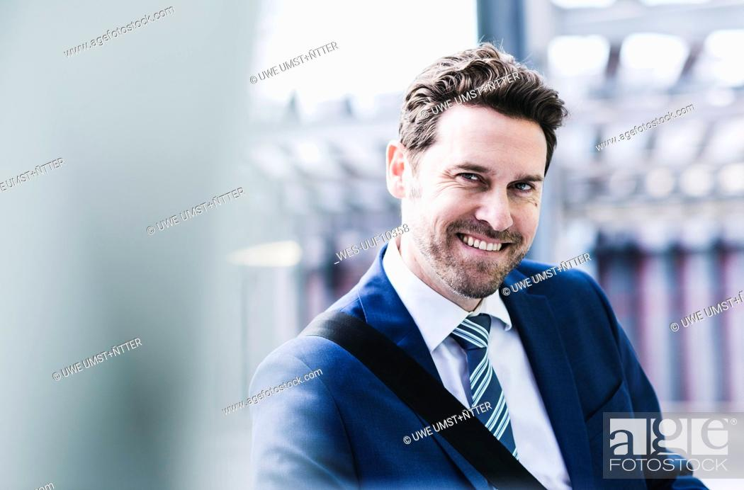 Stock Photo: Businessman standing on parking level, portrait.