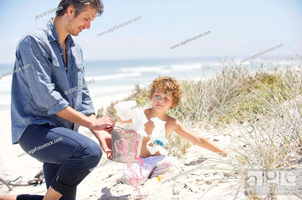 Stock Photo: Mid adult man and his son cleaning the beach.