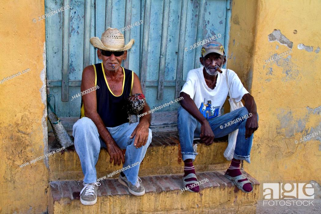 Stock Photo: Old Men with cigars sitting on stairs near Plaza Mayor, Trinidad Cuba.