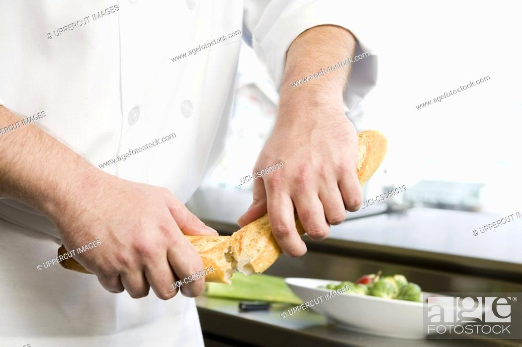 Stock Photo: Male chef breaking bread in half.