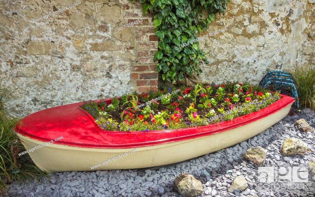 Stock Photo: Repurposed boat turned into a flowerbed, Beer Devon UK. June 2019.