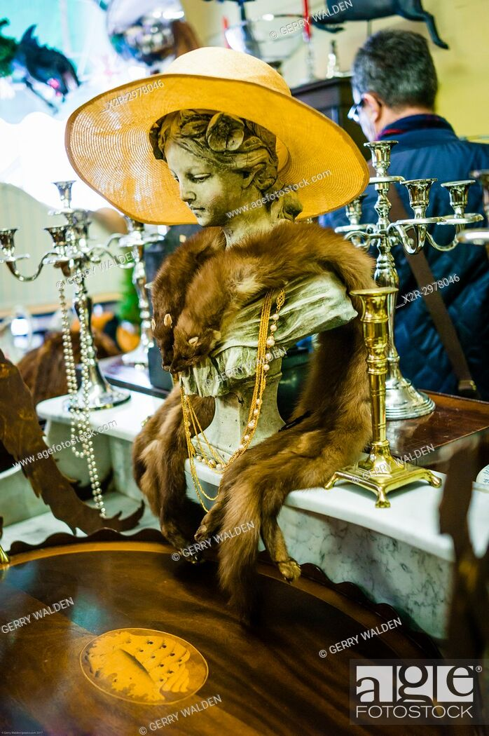 Stock Photo: Animal pelts and a yellow hat adorn an artistic bust inside an antique shop in Bath, Somerset.