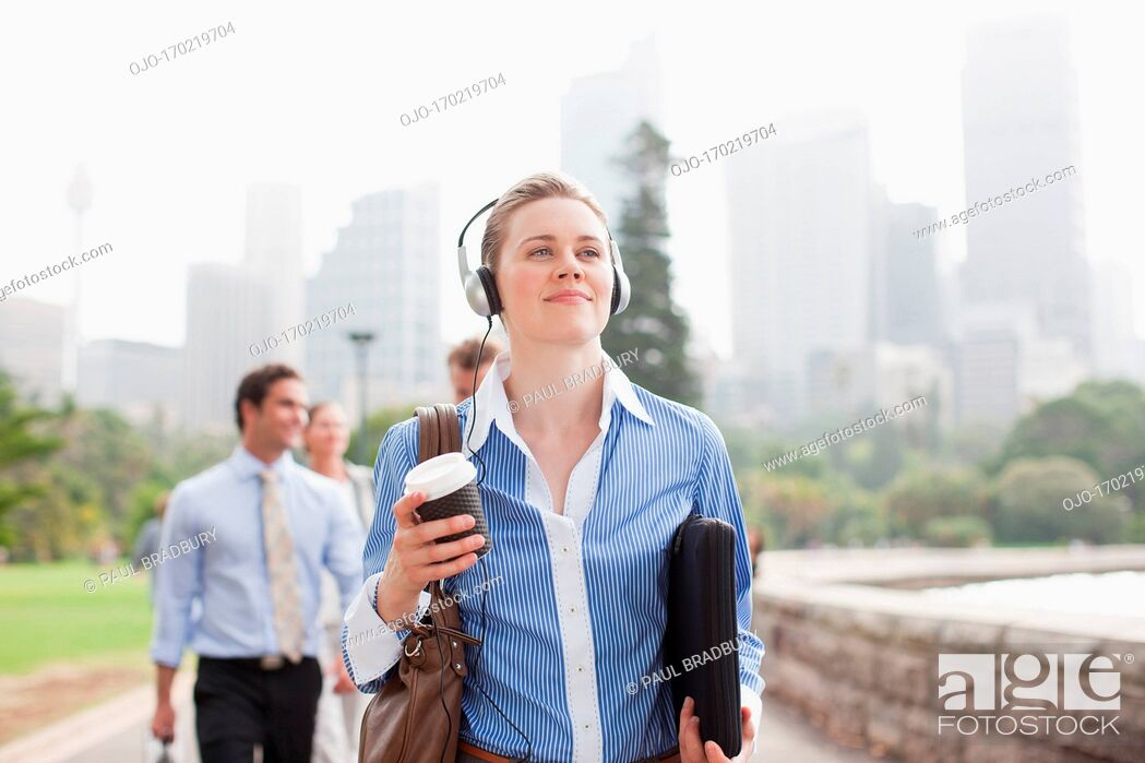 Stock Photo: Businesswoman listening to headphones and carrying coffee.