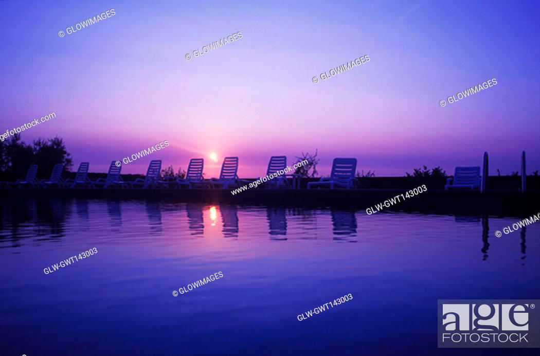 Stock Photo: Reflection of lounge chairs in water, Italy.
